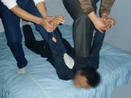 酷刑演示:掰,下巴担在床上,恶人再把受害人两手反背后面使两腿翘起