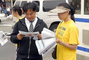 파룬궁수련생들에게 가한 폭력 배후세력에 대해 진상을 밝힌, 대기원 시보 특간을 읽고 있는 한 행인