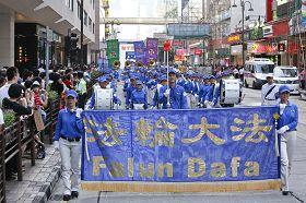 在天国乐团领头下,游行队伍走过繁忙的市区。