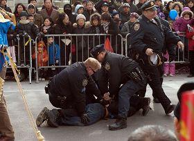 法拉盛新年游行活动中,一华裔男子从观众群中冲到法轮功队伍的前面,拉扯横幅并折断横杆。三个警察立即冲上去将其制服并逮捕。