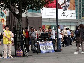 台湾法轮功学员在著名景点一零一大楼前讲真相炼功,许多大陆观光客专注观看播放的天安门自焚真相电视。