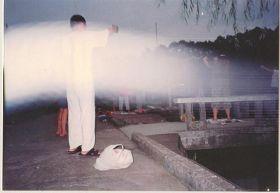 """'图一:一九九八年七月二十九日清晨,拍摄于湖南大学图书馆旁的法轮功炼功点,学员们正在炼第二套功法的""""头前抱轮""""动作。当日为阴天,照片中清晰可见巨大的银白色光束(能量罩),笼罩着整个炼功点'"""