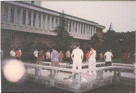 """'图二:一九九八年七月二十九日清晨,拍摄于湖南大学图书馆旁的法轮功炼功点,学员们正在炼第二套功法的""""腹前抱轮""""动作。照片中左下方,照相机拍到一个大光球(法轮)'"""