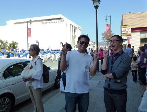 '向游行队伍竖起大拇指的华人观众'