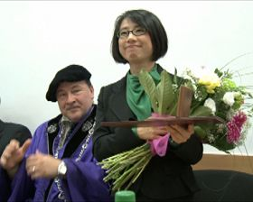 '张凤英女士的女儿丽萨代表母亲领取褒奖,后为校长格勒茨麦利博士'