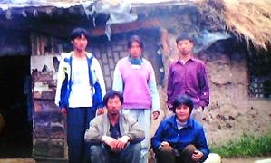 韩宝贵(前左一)一家在草房前。