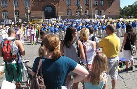 '法轮功学员在丹麦哥本哈根议会广场的反迫害集会吸引了民众驻足观看'
