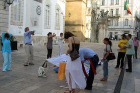 Coimbra的民众看真相展板和演示<span class='voca' kid='86'>功法</span>,签名支持反迫害