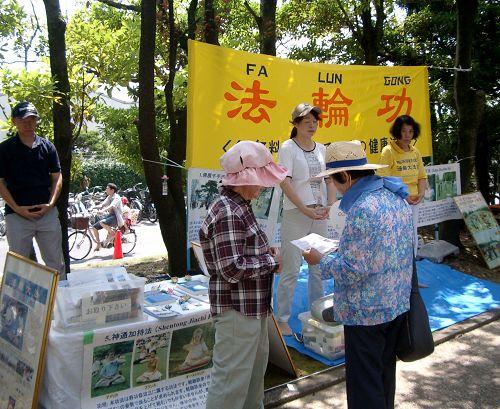 图2:学员们在第十八届稻泽夏季活动节展位上向市民介绍法轮功
