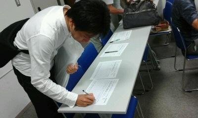 与会者在呼吁制止中共活摘法轮功学员器官的签名纸上签字