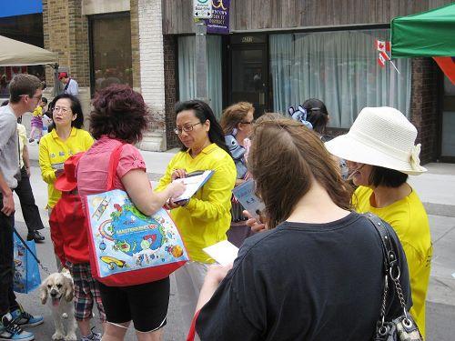 '多伦多法轮功学员展开征签活动,呼吁人们共同制止中共活摘器官的罪恶。'