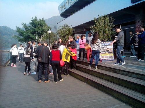 学员在伊达邵游客中心举真相展板,大陆游客在休息、等待时会驻足观看。