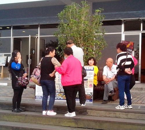 大陆游客在休息时观看展板,并与学员(中坐者,穿黄衣服)交谈,了解真相。