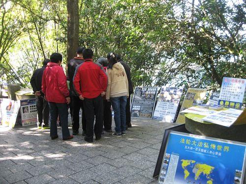 玄光寺步道上摆放很多真相展板,大陆游客正聚精会神的观看并讨论。