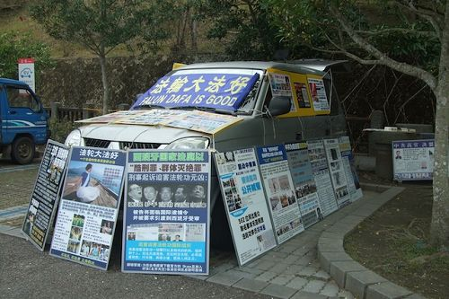玄光寺停车场上摆满真相展板的车子,后座还有一台电视不断播放真相,常有游客停下脚步仔细观看。