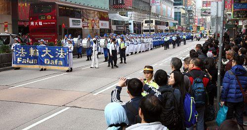 法轮功阵容庞大整齐的游行队伍吸引中西游客及港民驻足观看,纷纷举起相机、手机拍照。