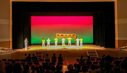 图1:法轮功学员在饭岛町文化节舞台上演示法轮功<span class='voca' kid='86'>功法</span>,并有学员在一旁解说。