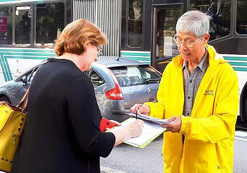 图4:萨拉(Sarah Nimoelc)在真相横幅前方的巴士站等车,她表示非常支持法轮功,并签名反迫害。