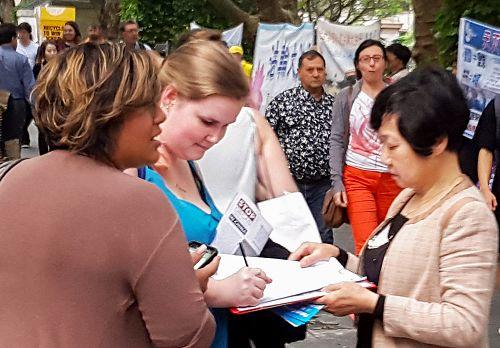 """图6:上班族女士凯丽和(Kirralee Hart,左)朋友瑞拉(Rawla O,中)分别签名反迫害,并表示:""""这么残酷的迫害持续十六年了,太恐怖了,我将会传播这个信息给所有的朋友知道,一起制止迫害。"""