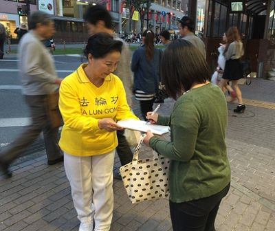 图1-2:日本民众听了法轮功学员讲迫害真相后,签名举报迫害元凶江泽民