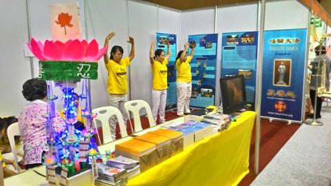 泰国健康与美容展上,法轮功学员在展位中演示<span class='voca' kid='86'>功法</span>