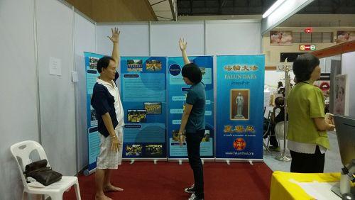 泰国健康与美容展上,参观者向法轮功学员学炼功法