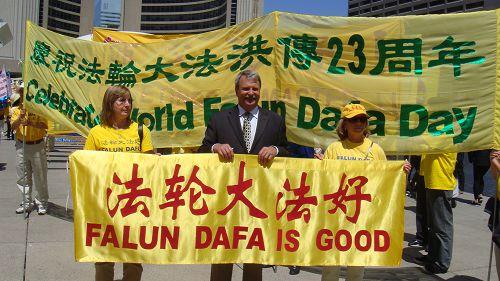 安省议员麦克拉伦(Jack Maclaren)和法轮功学员一起拉起了横幅走在游行队伍里。