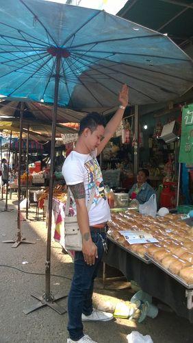 Korat市一面包店小伙照着法轮功真相传单学动作
