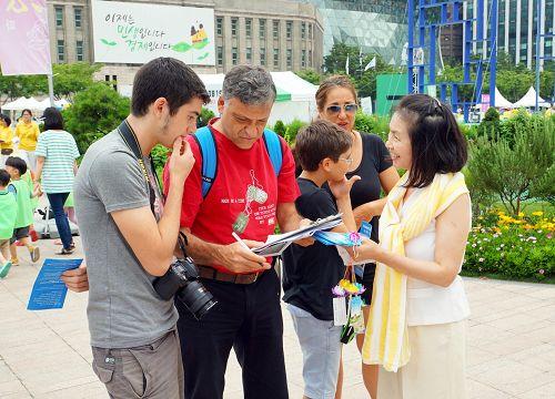 图16:以色列游客lebovits一家从学员那了解到法轮功真相后,都在联署书上签了名。