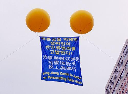 """图10:活动现场首尔广场上空飘扬着""""刑事举报江泽民迫害法轮功反人类罪行""""的大型气球。"""
