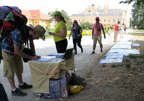 游客们在观看法轮功真相展板并在请愿信上签字