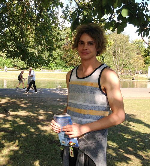二零一五年八月二十二日,罗马青年麦克在英国伦敦摄政公园法轮功炼功点第一次学炼法轮功,手拿意大利版的《法轮功》和法轮功学员制作的手工莲花,高兴地笑了