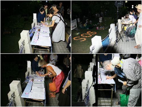 烛光守夜活动中,人们在继续签名支持法轮功