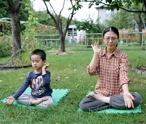 图2:摆脱乳癌忧郁困扰获新生的林雪和儿子在后院打坐。