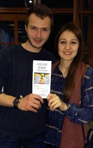 两位大学生Didem Yurtsever 和Kerim Koc手持法轮功传单合影,表示希望开始学炼