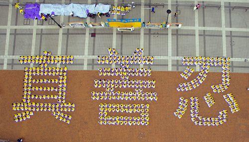 """二零一六年一月十六日,香港和来自亚洲多个国家地区的数百名法轮功学员,于法会前夕,在香港中环爱丁堡广场上排出""""真善忍""""三个大字并且集体炼功,场面殊胜祥和。"""