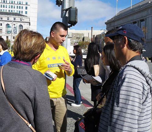 '图1:罗马尼亚法轮功学员DorianFillip向游客讲真相'