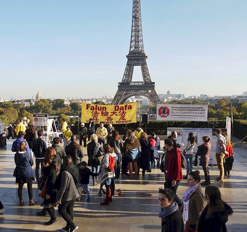 '图1:巴黎人权广场上游人驻足了解法轮功真相'