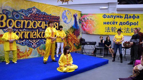 法轮功学员在展会的舞台上展示了五套功法