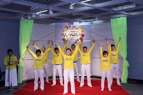 法轮功学员在舞台演示法轮功的五套<span class='voca' kid='86'>功法</span>动作