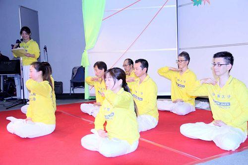 法轮功学员在舞台演示法轮功的五套功法动作
