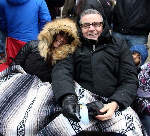 """圖10:多倫多的Paul和妻子裹著被子在看遊行,他說:""""天國樂團的演奏非常震撼人心,令我感慨的是這麼冷的天他們還能吹得這麼好聽,在給在寒冷中的我們帶來溫暖。"""""""
