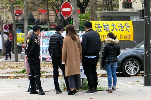 图1-3:来巴黎旅游的中国大陆游客经过世界著名的埃菲尔铁塔附近的法轮功真相点时,许多人驻足阅读真相展板,了解真相。