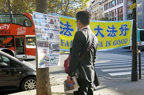图4-8 :来巴黎旅游的中国大陆游客经过世界著名的埃菲尔铁塔附近的法轮功真相点时,许多人驻足阅读真相展板,了解真相。