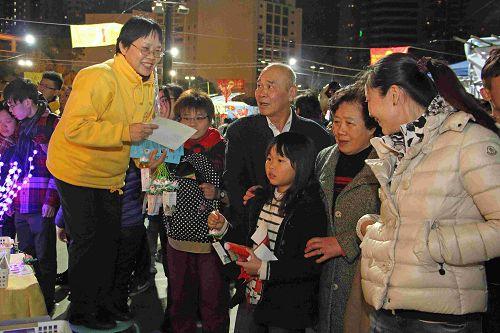 市民一家老少高高兴兴的接过法轮功学员送出的真相小莲花及资料。