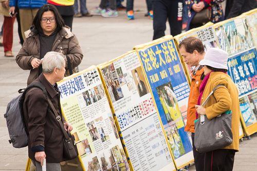 图5-6:与此同时,学员们在活动现场摆放了真相展板,吸引众多民众与国外游客、尤其是中国大陆游客驻足观看。