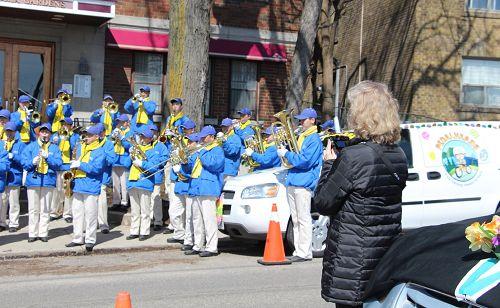 图8:多伦多市民Christina在起点处观看天国乐团排练时,一直拿着手机在录像。