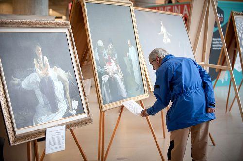 参观者认真了解画作和法轮功真相