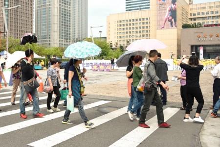 图7-8:法轮功学员在台北市政府前的市民广场举办纪念四二五和平大上访十七周年活动,吸引大陆游客拍摄观看