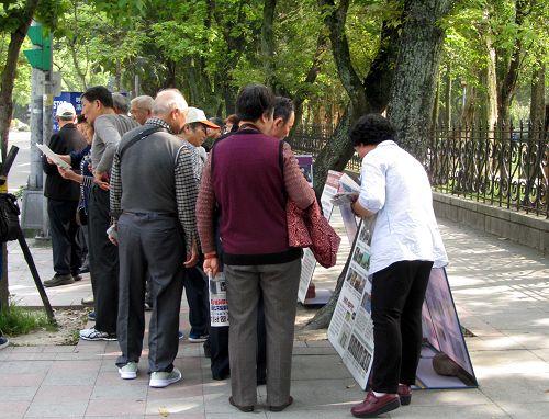 图5:中国游客仔细聆听法轮功学员讲真相。